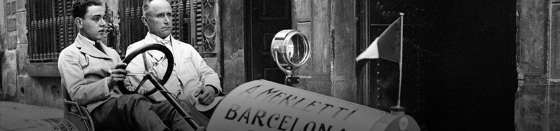Merletti i el seu fill dins el seu cotxe, davant la porta de casa seva al carrer Tapioles. Barcelona, Anys '20. Ref. ACP-1-881